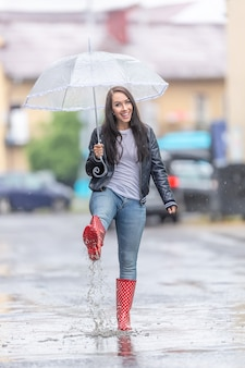 Happy woman in red polka dot rainboots  walks on the street with an umbrella on a raidy day.