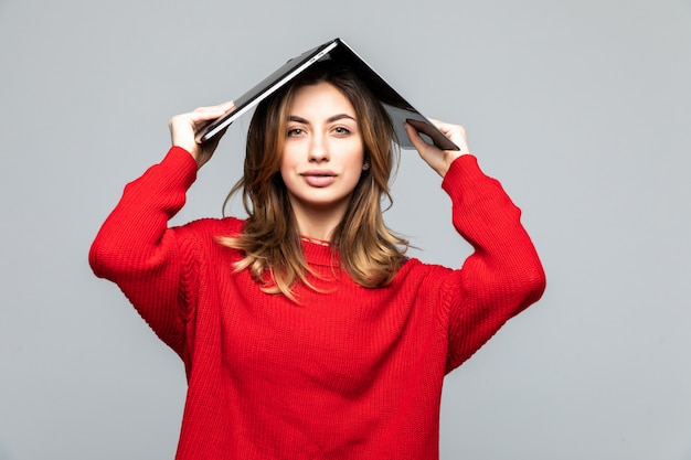 Happy woman in red sweater holding laptop above her head like a roof over gray wall.