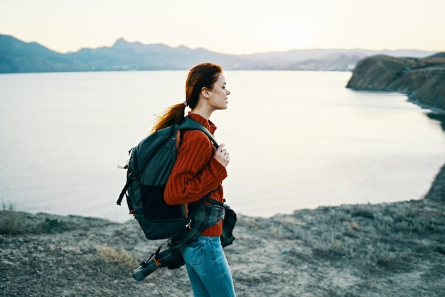 Happy woman in a red sweater with a backpack on her back resting in nature near the sea and mountains in the distance. high quality photo
