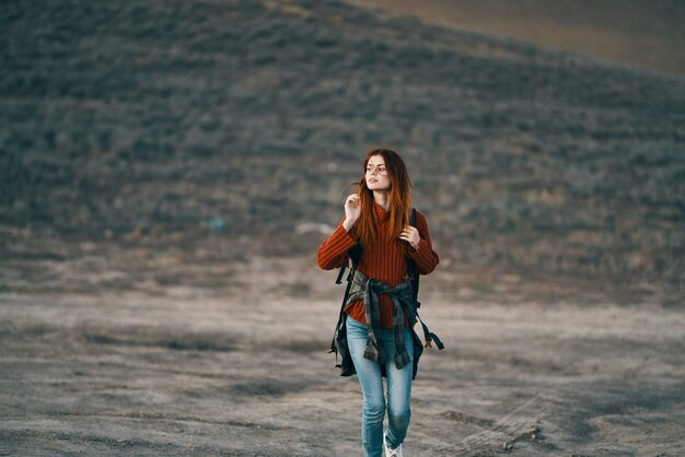 Happy woman in red sweater with backpack on her back resting in nature