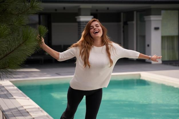 현대적인 빌라의 수영장 근처에서 시간을 보내는 동안 행복한 여성이 기뻐합니다. 아침에 기분이 좋은 생강 여자