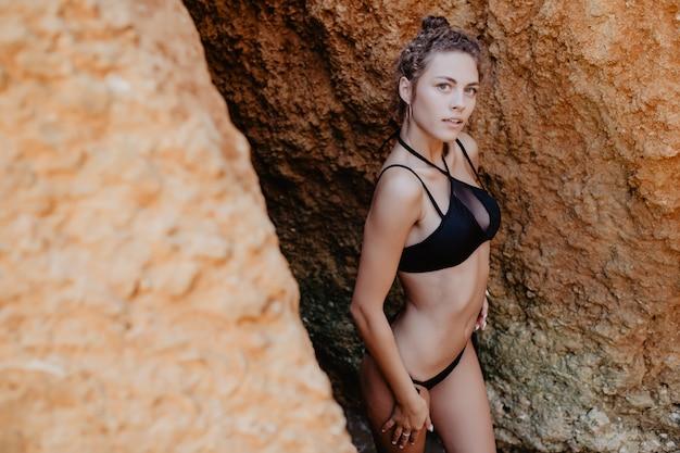 幸せな女はリラックスしてビーチで日光浴を楽しんでいます。