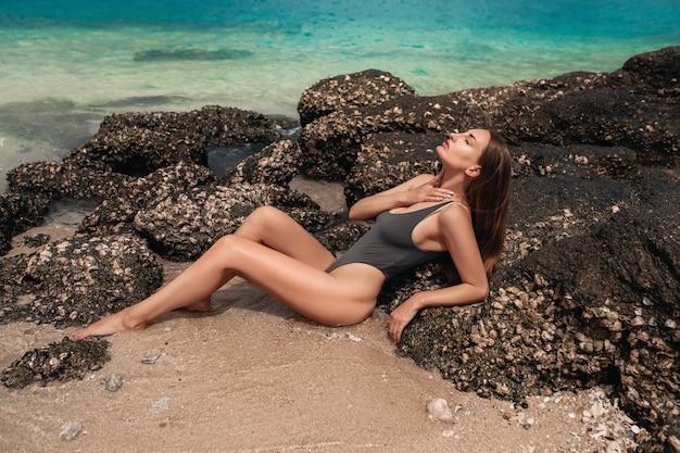 リラックスしてビーチで日光浴を楽しんで幸せな女