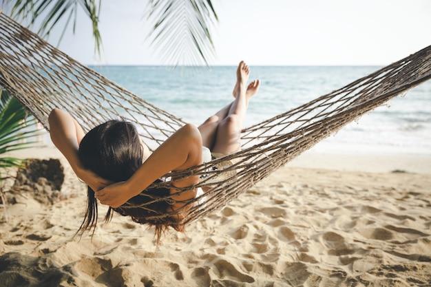Счастливая женщина, расслабляющий в гамаке