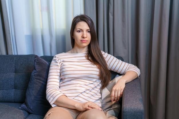 家でストレスのない週末を楽しんでいる快適な柔らかいソファでリラックスした幸せな女性落ち着いて満足