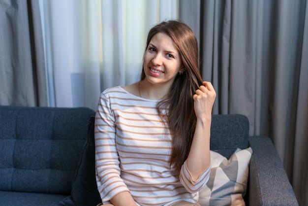 家でストレスのない週末を楽しんでいる快適な柔らかいソファでリラックスした幸せな女性は落ち着いて満足しています...