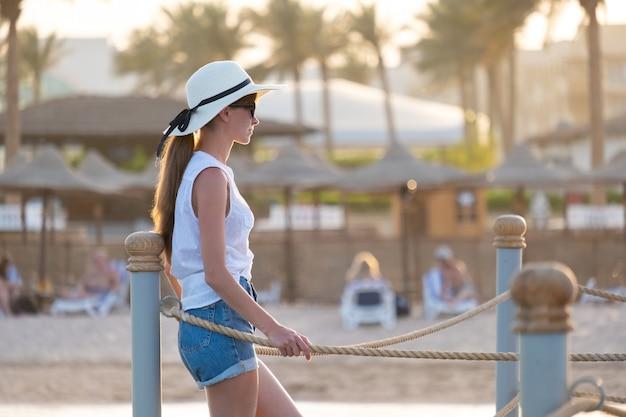 따뜻한 열대 저녁을 즐기는 해변의 호텔 데크에서 야외에서 휴식을 취하는 행복한 여성. 여름 휴가 및 여행 개념입니다.