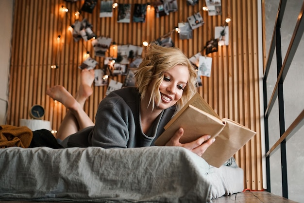 Happy woman relaxing and reading book on cozy bed - wooden wall and photos with lights - blurred background