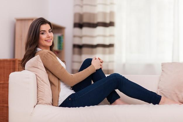 Donna felice che si distende sul divano
