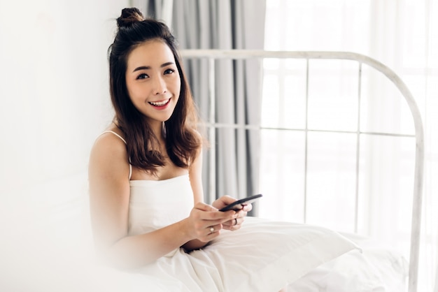 Happy woman relaxing and using smartphone on the bed at home