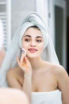 욕실에서 메이크업 클렌징 패드 로션 욕실 거울을 제거하는 행복한 여자