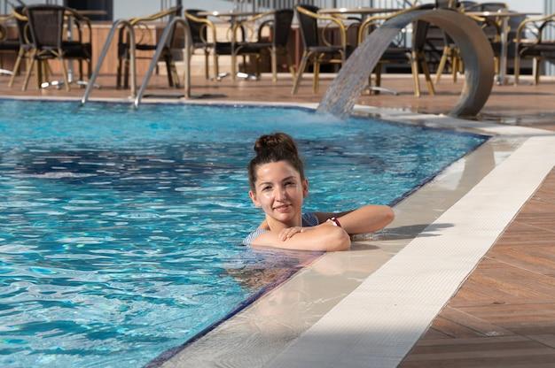 プールの端で休んで幸せな女性。