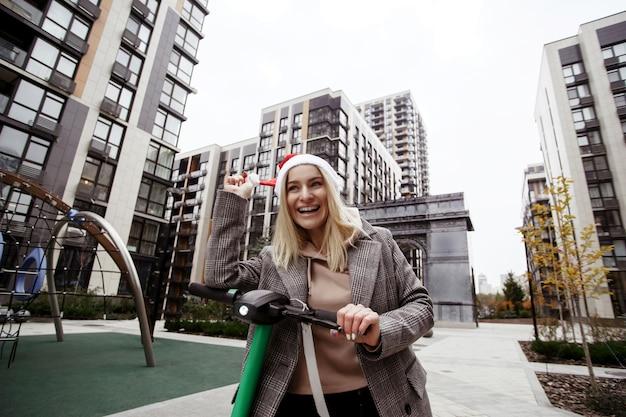 幸せな女性はクリスマスパーティーにレンタル電動スクーターに乗ります。彼女は赤いサンタの帽子を直し、笑いました。都市生活。友達に会いに行くカジュアルなコートを着た若い陽気なブロンドの女性。