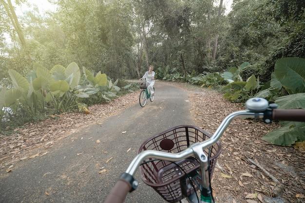 여름에 도로를 따라 자전거를 타는 행복한 여자.
