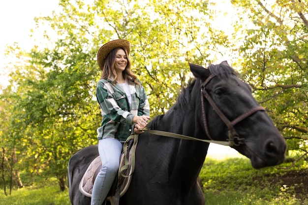 Happy woman riding horse medium shot