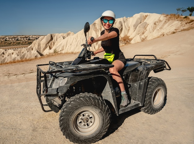 Happy woman riding quad bike in cappadocia, turkey
