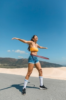 Happy woman on road turning hula hoop