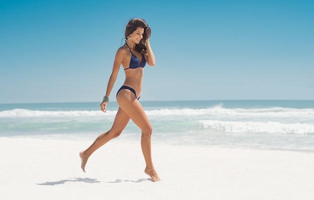 ビーチを走る幸せな女