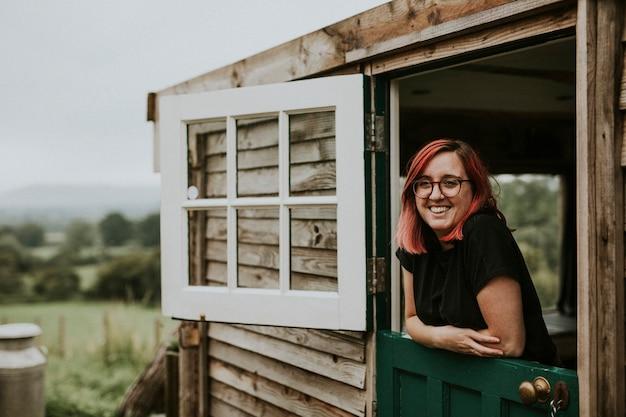 Donna felice in una casa di legno rurale