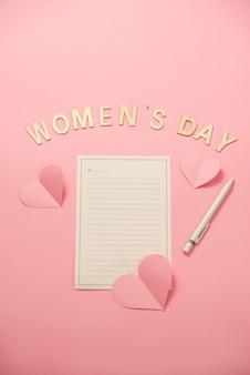 珊瑚紙の背景にハート紙と幸せな女性の日のメッセージ