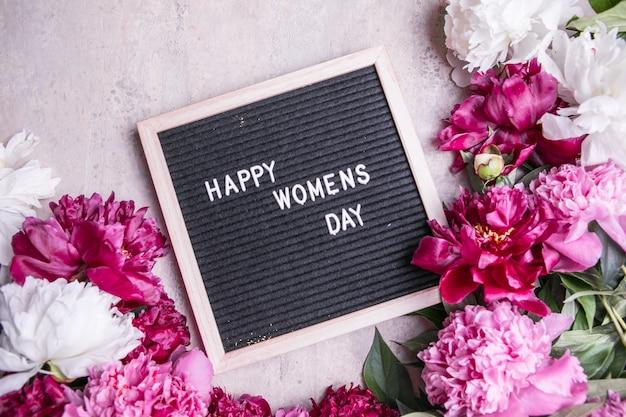 Счастливый женский день текст и пион. стильная цветочная открытка. рукописные надписи.