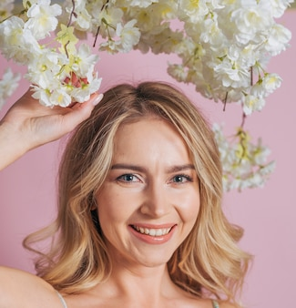 Happy woman's face holding bunch of white flowers