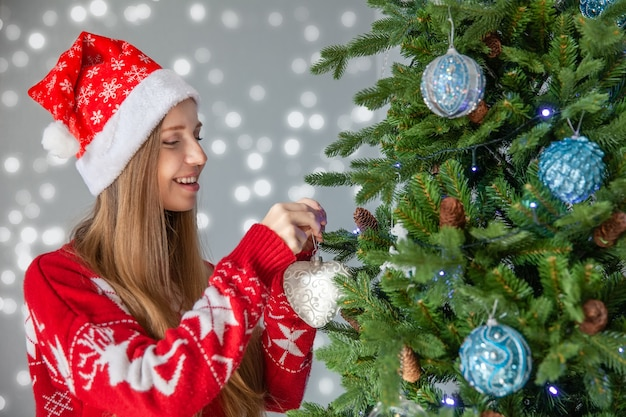 Happy woman in santa hat decorate christmas tree, concept of new year's holidays