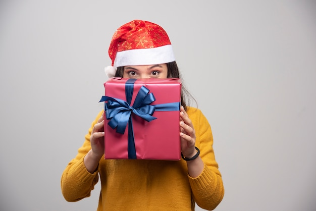 Donna felice in cappello della santa che si nasconde dietro il contenitore di regalo.