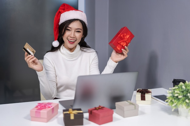 Happy woman in santa hat shopping online for christmas gift with laptop