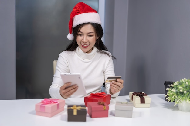 Happy woman in santa hat shopping online for christmas gift with tablet