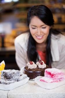 Счастливая женщина выбирая десерты от дисплея