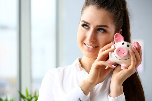 Happy woman shake in arms funny piggybank