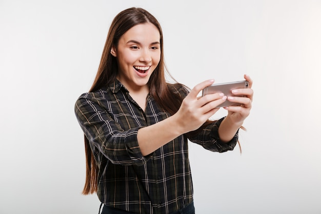 Donna felice in camicia che gioca sul telefono