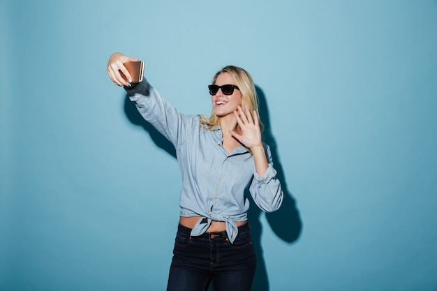 Happy woman in shirt and sunglasses making selfie on smartphone