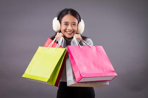 Счастливая женщина-покупатель с хозяйственной сумкой