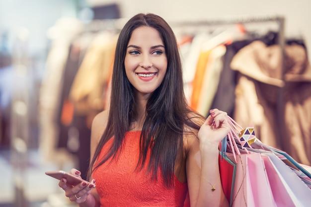 店で洋服を買う幸せな女性