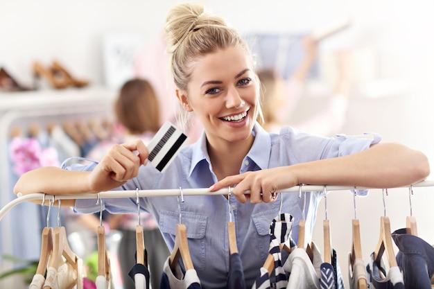 クレジットカードで服を買う幸せな女性