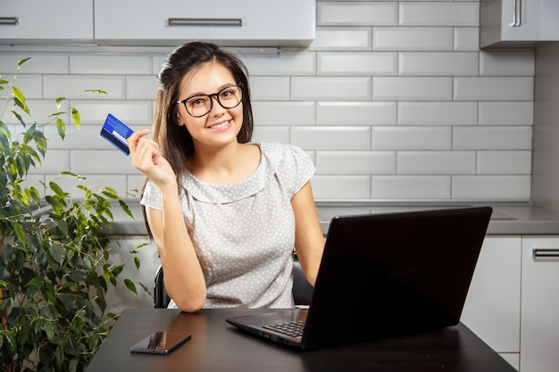 Happy woman shopping online with a credit card and laptop
