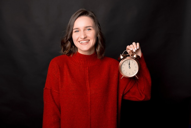 Happy woman showing alarm clock at midnight