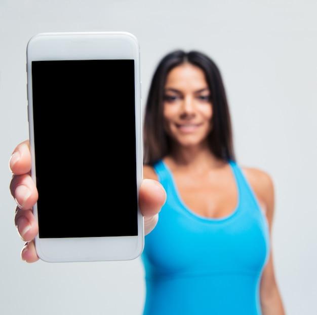 空白のスマートフォン画面を表示して幸せな女性