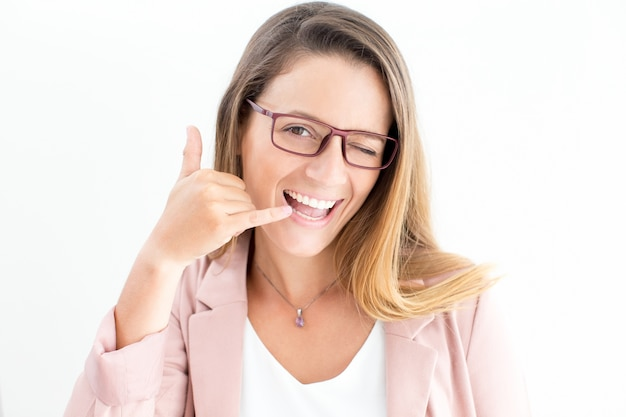 Happy woman showing call gesture and winking
