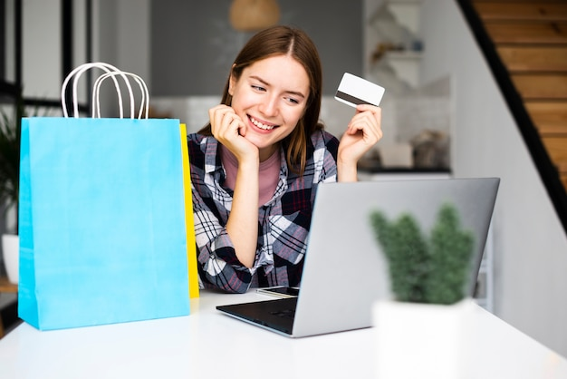 Happy woman showing credit card and looking at laptop