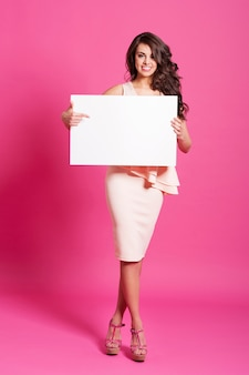 Happy woman showing at empty whiteboard