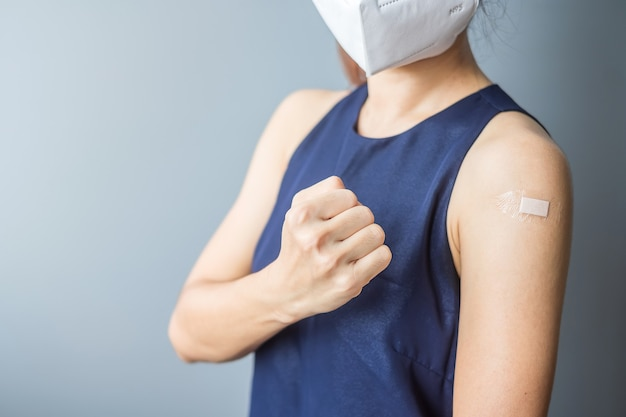 Счастливая женщина показывает знак кулака с повязкой после получения вакцины covid 19. вакцинация, коллективный иммунитет, побочные эффекты, эффективность, паспорт вакцины и пандемия коронавируса