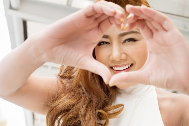 Happy woman showing love heart hand sign to you