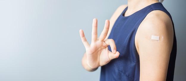 Счастливая женщина показывает знак ок с повязкой после получения вакцины covid 19. вакцинация, коллективный иммунитет, побочные эффекты, эффективность, паспорт вакцины и пандемия коронавируса