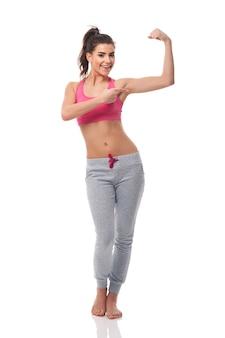 Счастливая женщина, показывая на ее бицепс