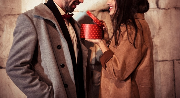 Happy woman showing present box to young man