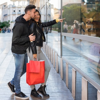 Happy woman showing on shop window to young man
