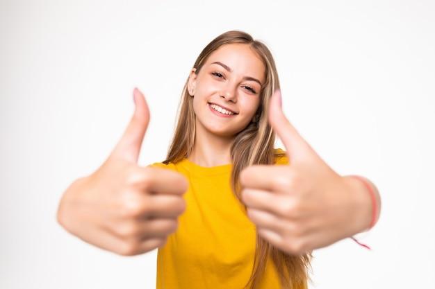 Счастливая женщина показывает палец вверх символ двумя руками. изолированные на белой стене